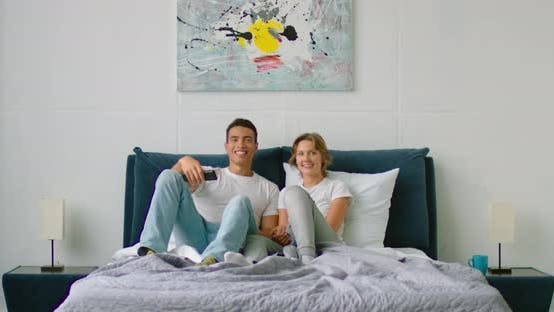 Thumbnail for Latin Man and White Woman Are Watching TV in Bedroom