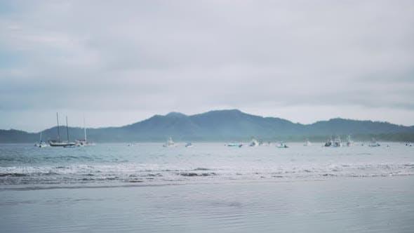 Thumbnail for Hintergrundplatte von Booten rollen auf ruhigen Meereswellen und Berge am Horizont