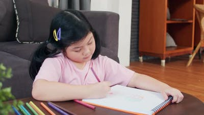 Young Asian girl drawing at home relax rest fun happy draw cartoon in sketchbook.