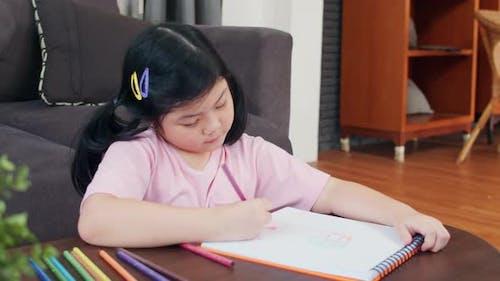 Junge asiatische Mädchen zeichnen zu Hause entspannen sich Ruhe Spaß glücklich Zeichnen Cartoon im Skizzenbuch.