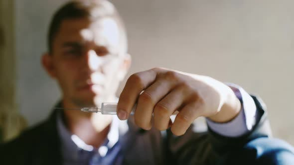 Thumbnail for A Young Man Holding a Syringe with a Drug. Concept: the Willpower To Quit Drugs, Danger, Crime