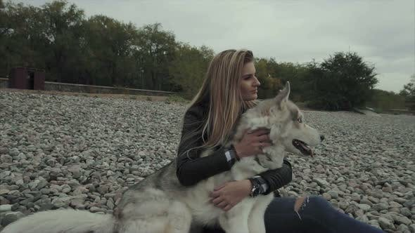 Young Pretty Woman with Siberian Husky Dog Sitting on the River Bank