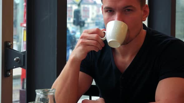 Thumbnail for A Young Handsome Man Sits at a Table with Meal in a Cafe, Drinks Tea and Smiles at the Camera