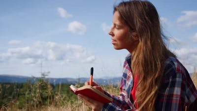 Girl Making Notes in Notebook