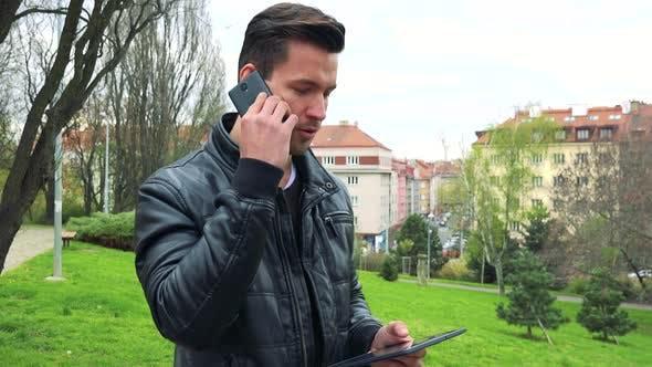 Thumbnail for Junge gutaussehende Mann steht, spricht mit jemandem am Telefon und hält einen Tablet-Computer