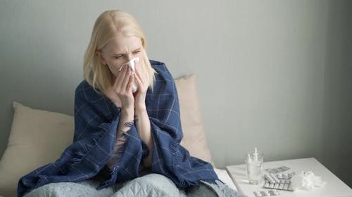 Young Woman with Flu Coughing Sitting on the Bed
