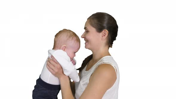 Thumbnail for Positive Little Cute Boy with Beautiful Mom Rising Her Baby Up on White Background.