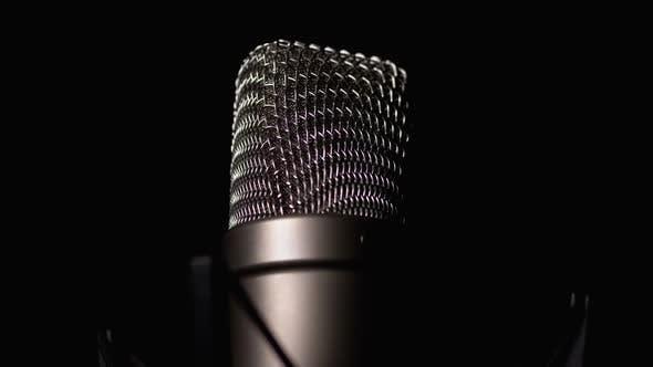 Studio Condenser Microphone Rotates on Black Background