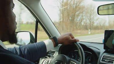 Confident African American Man in Suit Driving Car on Freeway