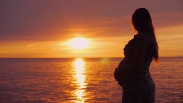 Thumbnail for Young Pregnant Woman with a Big Belly Looks at the Majestic Sunset Over the Sea