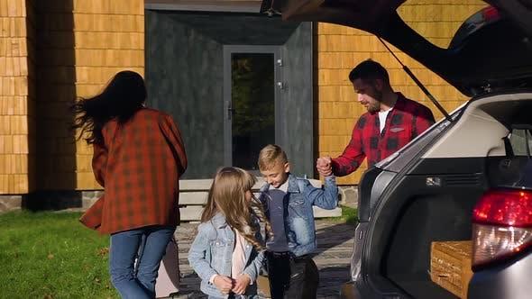 Thumbnail for Lächelnde Familie, die ihre Koffer in Kofferraum vor gemeinsamer Autofahrt laden