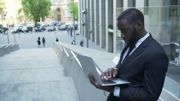 Thumbnail for Businessman Standing Outside Business Center, Working with Laptop Checking Files