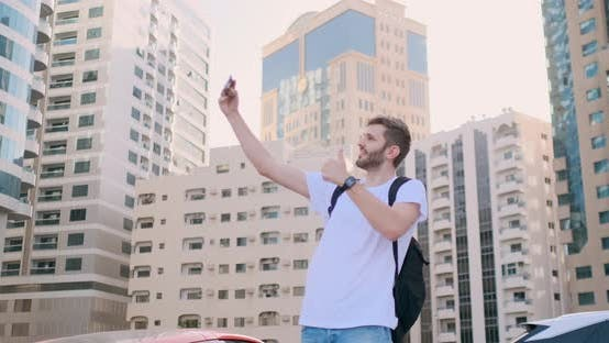 Thumbnail for A Young Man with a Backpack Takes a Selfie in the City