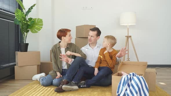 Happy Beautiful Family Relaxing on Floor While Moving Into New House