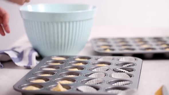 Scooping vanilla cupcake batter into cupcake liners.