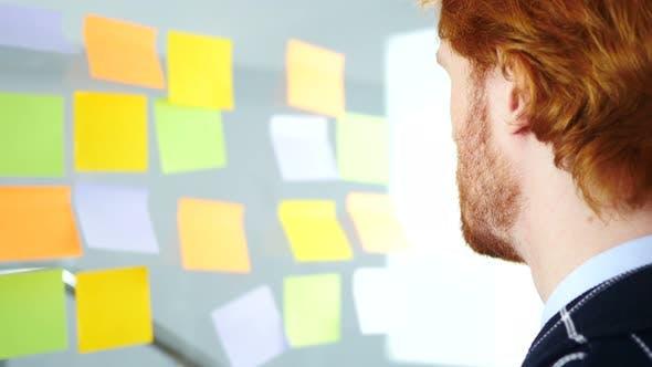 Thumbnail for Geschäftsmann Arbeiten an Haftnotizen befestigt auf Glas im Büro, Rückansicht