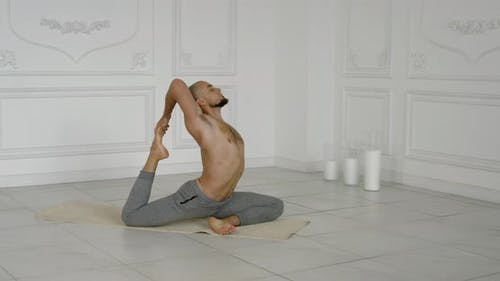 Male Master of Yoga Is Performing Asana on Floor Indoors