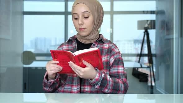 Muslim beautiful woman is reading the Koran.