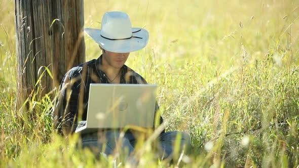 Thumbnail for Cowboy sits in grass using laptop computer