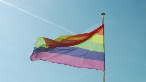 Big Rainbow Flag Gay Pride LGBTQ Developing By the Wind Against the Blue Sky