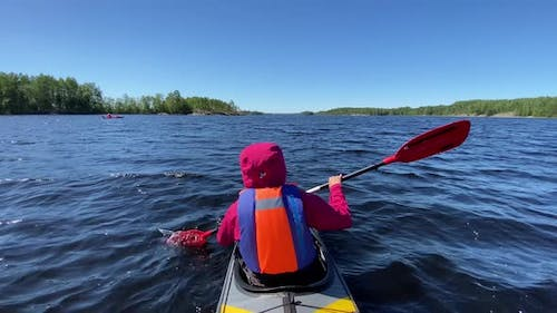 Person Rows Sports Kayak Along Lake Water Against Blue Sky