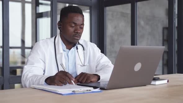 Black Male Doctor Consulting Patient By Telemedicine Online Videocall on Laptop