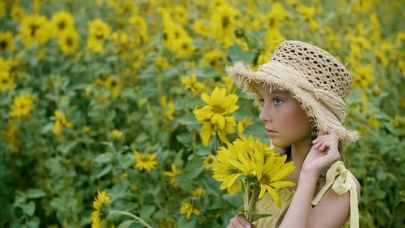 Thumbnail for Portrait Beautiful Girl in Straw Hat Holding Yellow Sunflowers on Flowering Field. Smiling Country