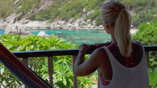 Girl Sitting in Hammock on an Terrace and Pointing with Her Hand the Beautiful Tanote Bay, Koh Tao
