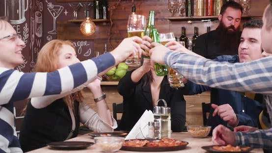 Thumbnail for Group of Happy Friends Rising Beer Mugs Up and Clinking Them