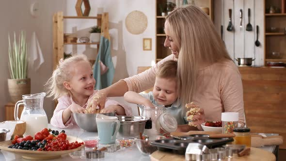 Caucasian Mom with Kids Making Batter for Baking Together