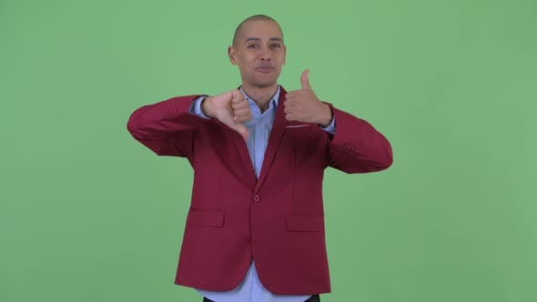 Thumbnail for Confused Bald Multi Ethnic Businessman Choosing Between Thumbs Up and Thumbs Down