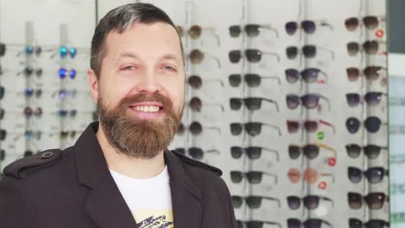 Thumbnail for Cheerful Mature Man Smiling To the Camera While Buying Sunglasses