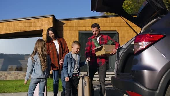 Thumbnail for Children Helping their Joyful Young Parents to Load Suitcases and Box with Green Plants Into Trunk