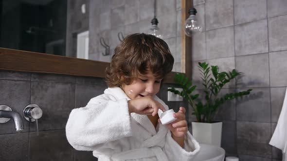 Thumbnail for 5-Aged Boy with Brown Curly Hair in Robe Playing with Mom's Cream in the Bathroom