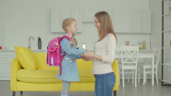 Loving Mother Cheering Up Schoolgirl at Home
