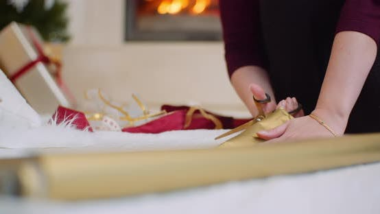 Thumbnail for Woman Cutting Golden Wrapping Paper At Home