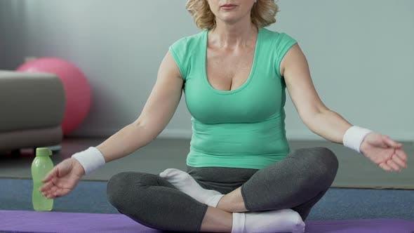 Thumbnail for Senior Woman Sitting on Yoga Mat in Lotus Pose, Active Lifestyle, Meditation