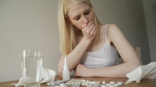 A Sick Woman Sits at Home with a Bunch of Pills Coughs and Blows Her Nose Into a Napkin