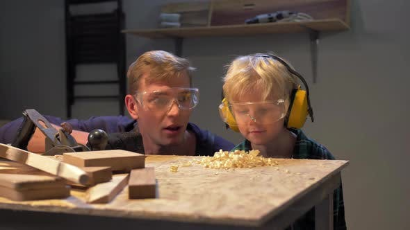 Thumbnail for Boy and Man Blow Off Wooden Shavings From the Table, Slow Motion