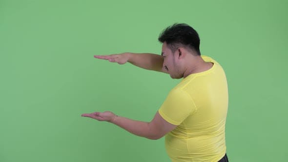 Thumbnail for Happy Young Overweight Asian Man Snapping Fingers and Showing Something