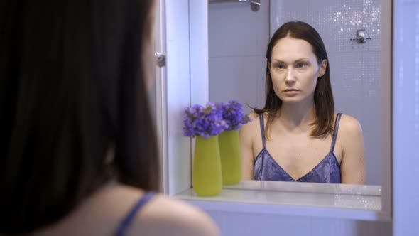 Reflection of Unhappy Pretty Woman in Mirror