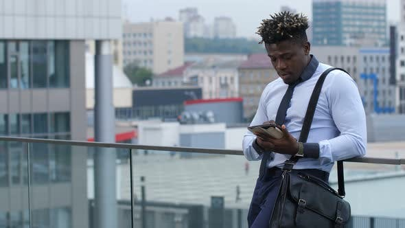 Thumbnail for Dark-skinned Businessman Text Messaging Outdoors