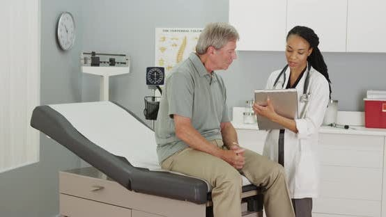Thumbnail for African woman Doctor talking with elderly patient