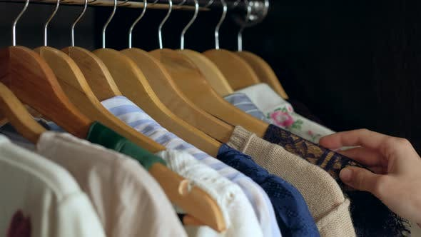 Woman Chooses Clothes in the Wardrobe