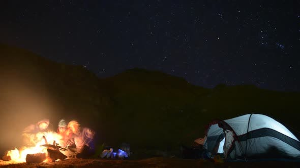 Thumbnail for A campfire near a tent and campground at night.