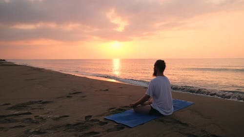 Man Sits in Lotus Position at Beach