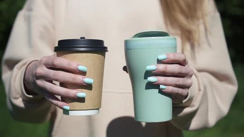 Close Up Girl Holding Two Cup Eco Friendly Reusable and Paper Coffee Disposable