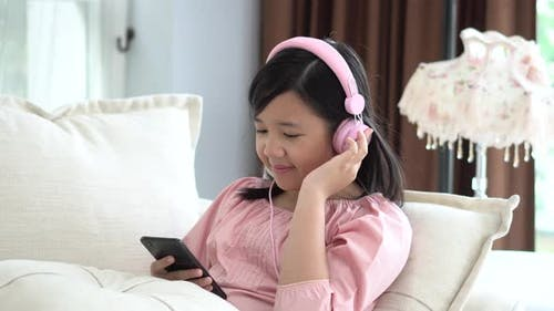 Beautiful Asian Girl Listening To Music  Sitting On A Sofa In The Living Room At Home