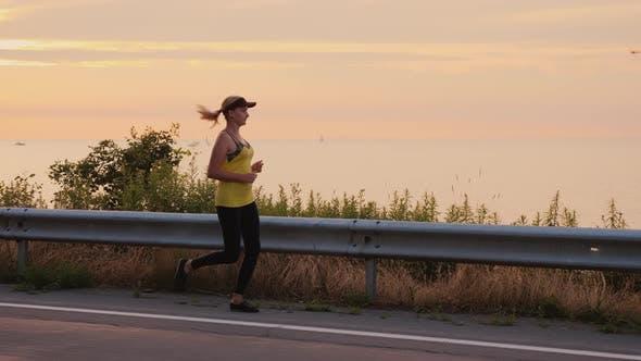 Thumbnail for Woman Makes an Evening Jog Along the Road Along the Lake