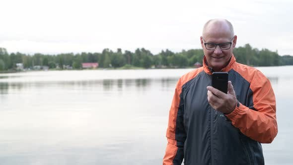Thumbnail for Happy Senior Man Using Phone And Thinking By The Lake